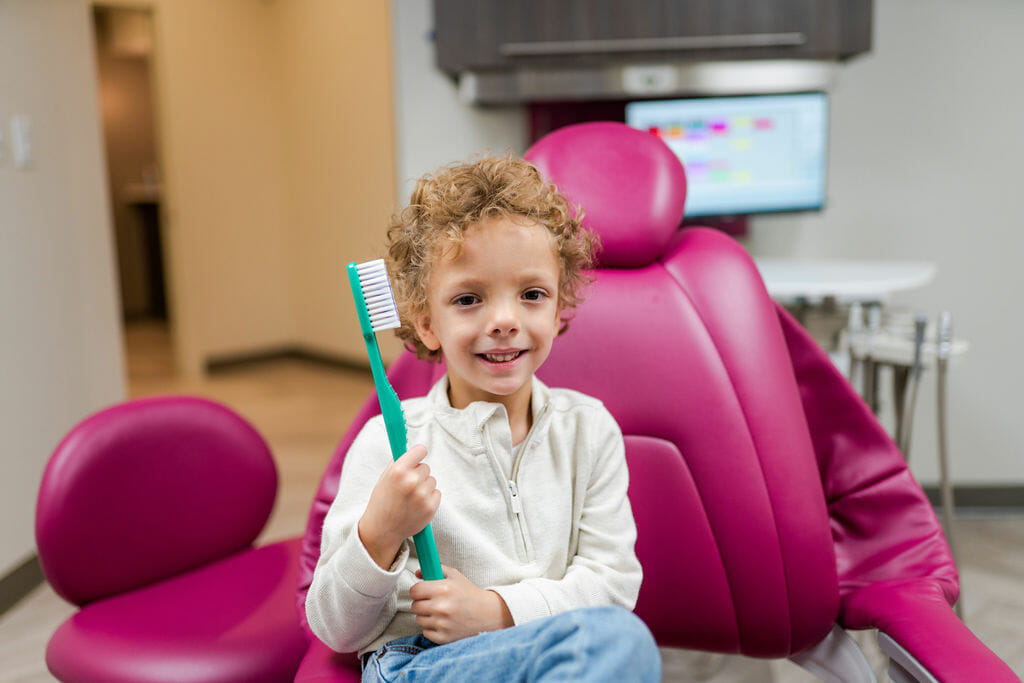 Young boy sitting in dental chair holding a giant green toothbrush