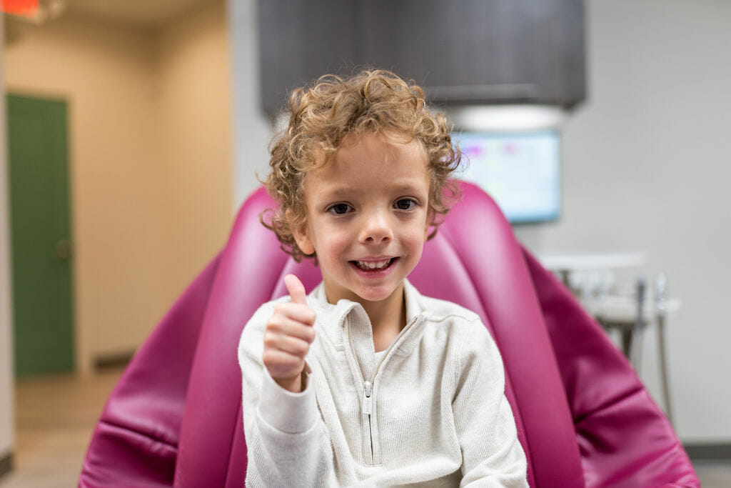 Curly haired boy sitting in dental exam room giving thumbs up to camera