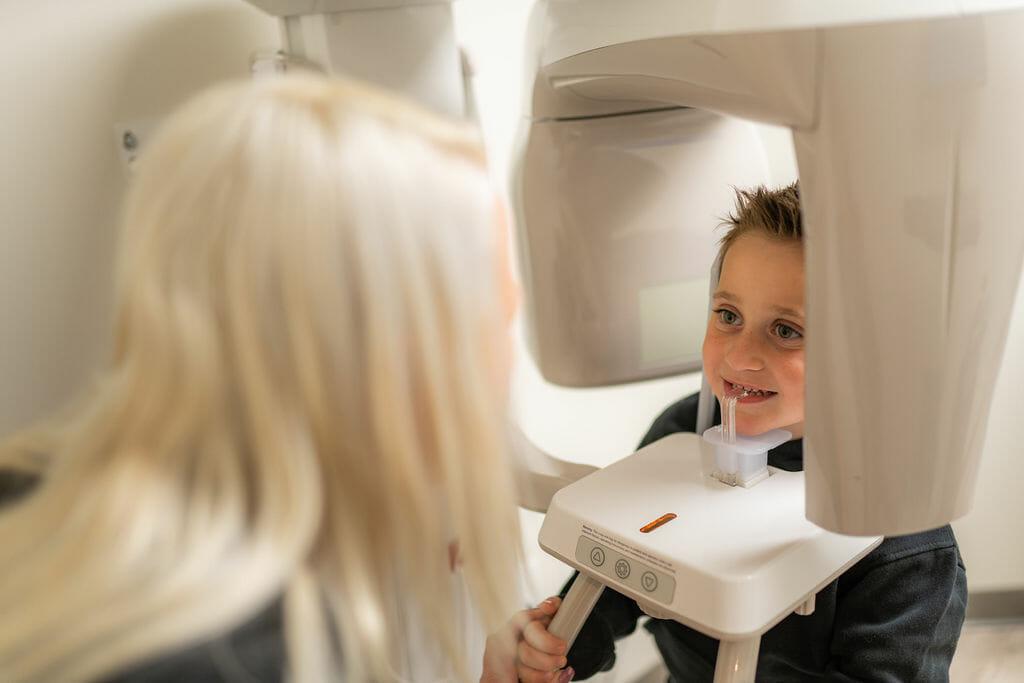 Dental hygienist preparing child for dental xray
