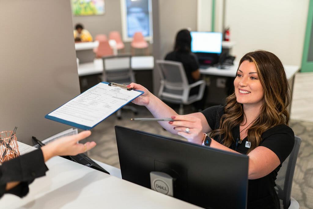 Front desk team member handing clipboard with paperwork to patient